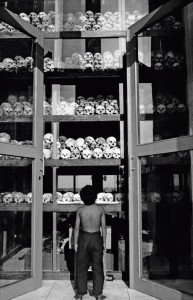 10 Feb 2004, Cambodia --- A child looks at the piles of skulls, victims of the Khmer Rouge regime, displayed at a memorial to the victims at the Choeung Ek killing fields. --- Image by © Andrew Holbrooke/Corbis